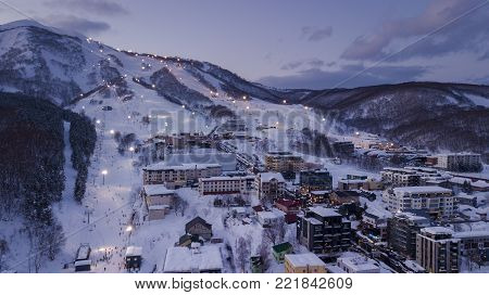 NISEKO, JAPAN - DECEMBER 22, 2017 : Aerial view at dusk of night skiing in Niseko Village. Niseko is a popular destination for ski resorts in Japan