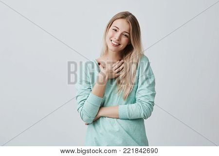 Portrait of happy blonde woman glad to recieve present from husband has joyful expression, smiles broadly with teeth. Beautiful pleased female model in light blue sweater expressing positive emotions poster
