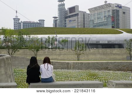 Seoul, South Korea October 05, 2017. Two Girls Sit In Dongdaemun Design Plaza Modern Architecture Bu