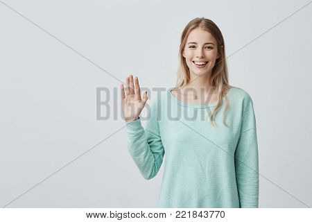 Young beautiful woman with long blonde hair congratulating her friend on her birthday. Pretty student girl saying hello, smiling joyfully and friendly, waving her hand