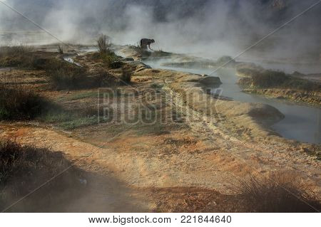 A blurred silhouette of a woman washing her hands in the hot mineral springs of Rupite. The water in the springs of Rupite is considered healing