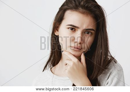 Young woman with dark hair and dark eyes frowning her eyebrows holding index finger on chin having doubtful and suspicious look, sceptical about something. Human emotions and face expression concept