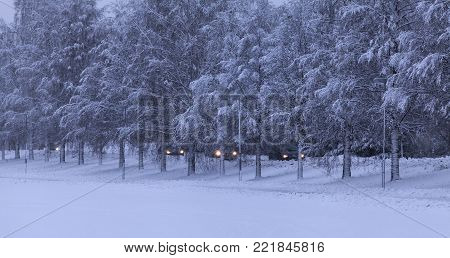 UMEA, SWEDEN ON DECEMBER 11. View of trees, street and the traffic in snowy condition on December 11, 2017 in Umea, Lights on. Editorial use.