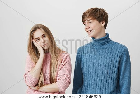 Love, romance and relationships concept. Studio shot of irritated blonde girl resting her head on hand, because she is dissatisfied with present from her smiling boyfriend. Body language and face expression.