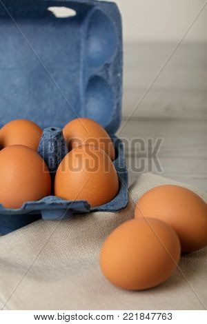 Chicken eggs in a blue package on a gray wooden background. Selective focus.