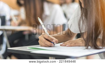 School student's taking exam, thinking hard, writing answer in classroom for educational university admission test  and world literacy day concept