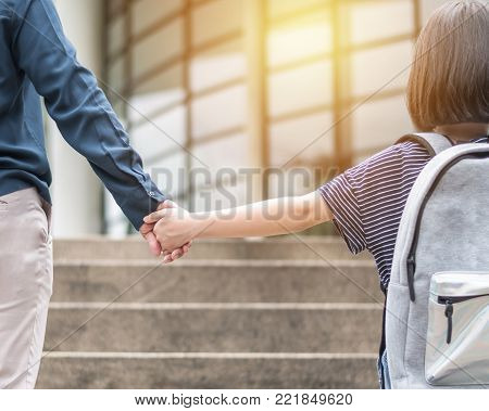 Girl kid (elementary student) carrying backpacks holding parent mother's hand walking up educational building's stair going to class for back to school first day and bring kid to work concept