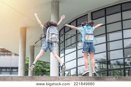 Happy school girl kids (elementary students) back view with backpacks jumping to celebrate going to class on first day of back to school education concept