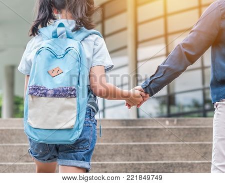 Back to school education concept with girl kid (elementary student) carrying backpacks holding parent woman or mother's hand walking up school building stair going to class
