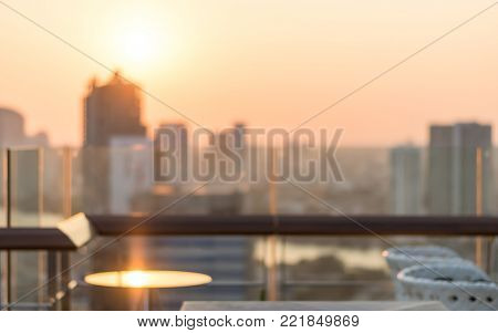 Rooftop party blur city view background from hotel balcony toward blurry restaurant dining table during sunset happy hour romantic golden sunset