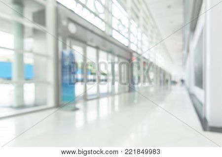 Office business building blur background of white empty room inside lobby hall interior, medical clinic hallway, or airport terminal corridor passage way with blurry light from glass wall window