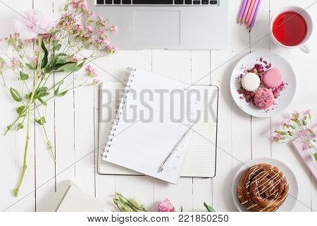 Feminine flat lay workspace with laptop, cup of tea, planner, macarons and flowers on white wooden table. Top view mock up.