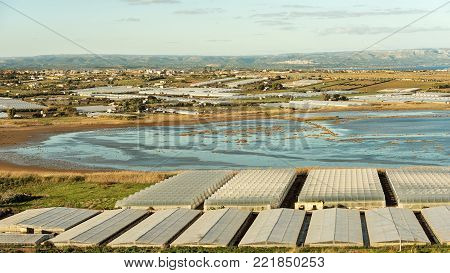Greenhouses for the cultivation of tomato and saline ponds in the countryside of Pachino Syracuse (Siracusa) - Sicily island, Italy, Europe