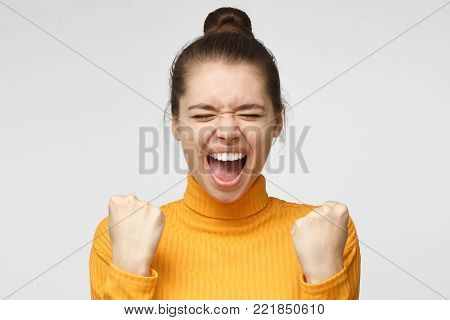 Girl power! Closeup of emotional woman isolated on gray background showing white teeth while screaming with joy and victorious expression, holding hands in gesture of winner, looking extremely happy
