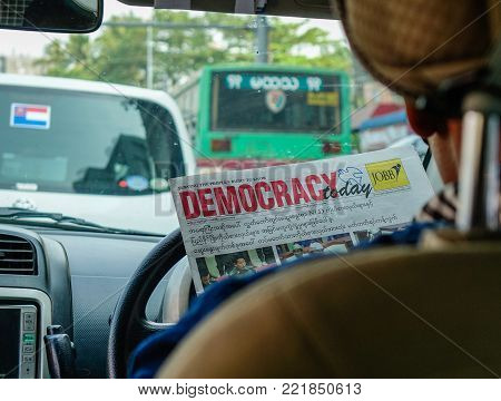 Yangon, Myanmar - Feb 27, 2016. Taxi driver reading news in car in Yangon, Myanmar. Yangon also called Rangoon city capital of independent Myanmar (Burma) from 1948 to 2006.