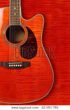 Musical instrument - Silhouette of a orange flame maple tiger maple acoustic guitar with cutaway on a flame maple background.