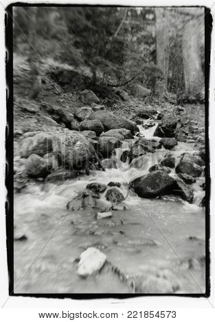 The mountain river flows through the rocks. Attention! The image contains granularity and other artifacts of analog photography!