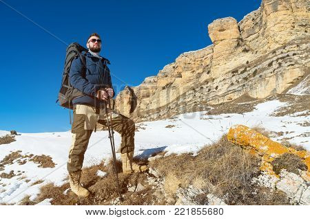 A hipster traveler with a beard wearing sunglasses in nature. A man hiking in the mountains with a backpack and Scandinavian walking sticks in the background of a mountain landscape and blue sky. Travel lifestyle adventure outdoor recreation outdoor sport