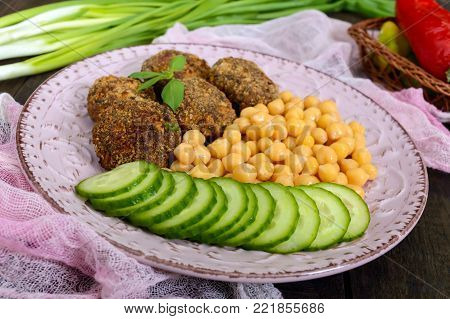 Tasty meat cutlets, chickpeas, fresh cucumber on a ceramic plate on a dark wooden background.