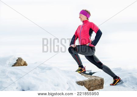 Woman runner stretching legs before run. Young athlete woman working out. Fitness concept. Sports and activities in winter or autumn time.