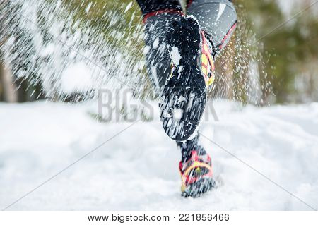 Legs of a young runner outside in winter nature.