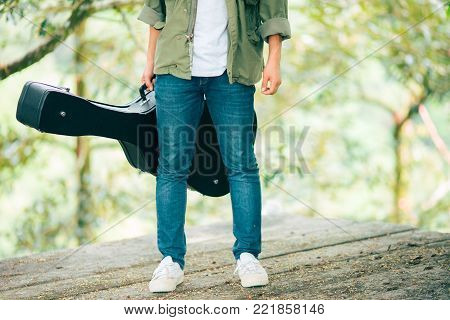 Man dressed in jeans holding guitar case in nature outdoo