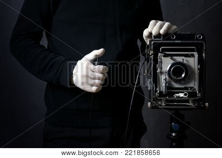 photographer in white gloves takes a picture on a retro camera, on a black background