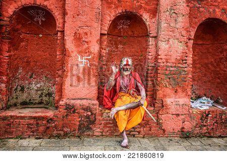 KATHMANDU, NEPAL - OCTOBER 21, 2015 : Wandering Shaiva sadhu with traditional face painting in ancient Pashupatinath Temple