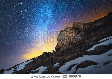 Night scenery done on long exposure. A beautiful Caucasian landscape of red rocks against the background of the cold milky way and a warm yellowish red glow on the horizon behind the rocks. The concept of beautiful Caucasian nature in the bright colors of