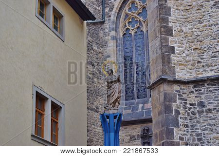 Sculpture of the Virgin Mary with a wreath of flowers on the pedestal next to the temple in Prague. Czech Republic.