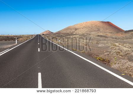 A road in Lanzarote cutting through a volcanic desert area with the Montana Colorada on the right, Canary Islands, Spain