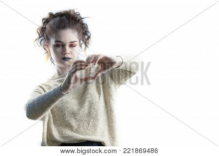Portrait of a young caucasian girl with a heart symbol from her fingers, critically examining and analyzing her love. Weighing all the pros and cons of the relationship. Isolated on white background.