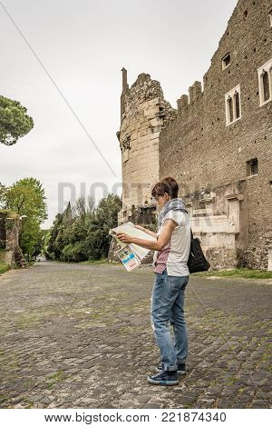 Tourist With Map Getting Around Ancient Ruins In Rome Old Town, Appia Antica Way, Heritage Of Early
