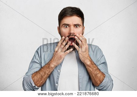 Frightened Bearded Male Brunet Covers Widely Opened Mouth Nervously, Exclaims With Anger, Dressed In