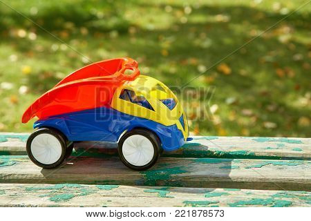 Colorful toy truck on grass background.  babycar outdoors