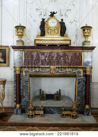 Saint Peterburg, Russia - JUNE 12, 2013: Marble fireplace with clock in Hermitage museum Saint Peterburg