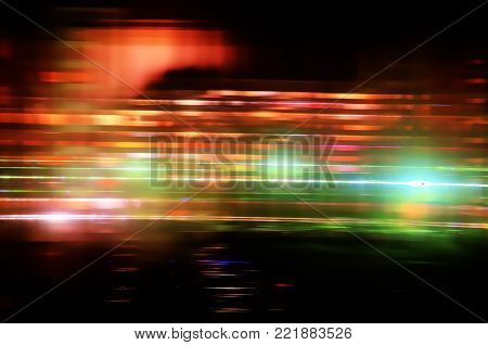 Multicolored abstract background blur of street lights in motion. Multicolored striped lines and spots. View through the window of polycarbonate, Long exposure.