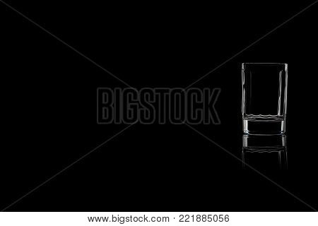 A small shot of vodka or tequila on a black background. Place for your text.