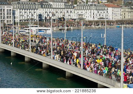 LUCERNE, SWITZERLAND - FEBRUARY 20, 2012: View to the crowd of people at the bridge watching the parade during carnival in Lucerne, Switzerland.