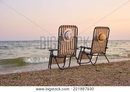 Sea, sky, beach with beach chairs on morining, back view. Sea waving on beach chair. Vessel on skyline.