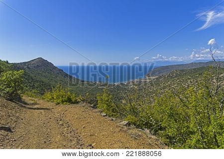 A dirt road leading to the sea. Crimean mountains. Sunny summer day.