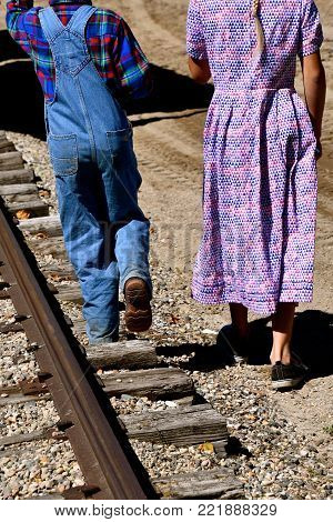 An unidentified young lad in bib overalls and a young girl in an ankle length gingham dress walk along the railroad tracks