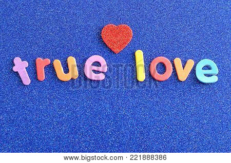 The words true love in colorful letters on a blue background with a red heart