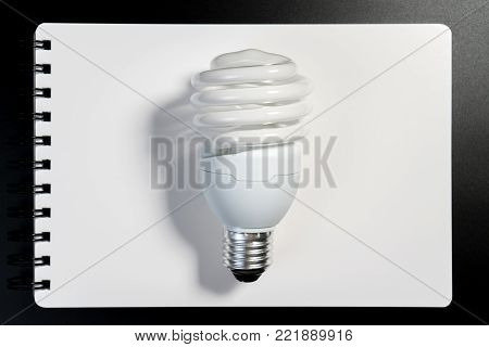 One fluorescent light bulb on white notebook paper on black background for energy saving concept. Light bulb on white book for business and education thinking idea concept.