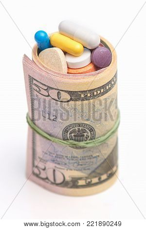 Wrapped Dollars And Medicine Pills Over White Background. Paid Medicine And Corruption Concept. Doll