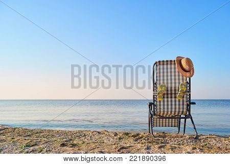 Back view woman's hat on deck chair and attached flip flops. Concept of beach accessories.