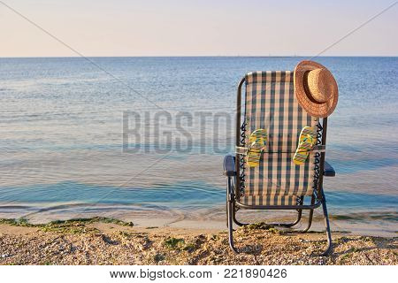 Back view chaise-longue and beach accessories near the sea. Checkered deck chair, attached flip-flops and sun hat on top.