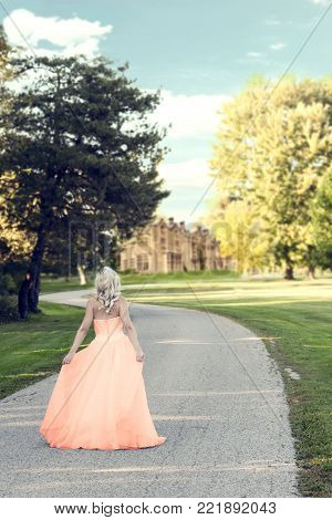woman in evening dress walking to manor house