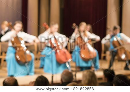 Ensemble of cellists. Guys and Girls Blurry
