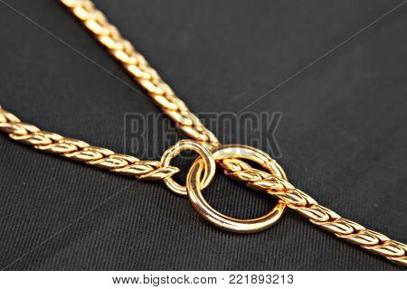 Gold choke chain for dog isolated on black background